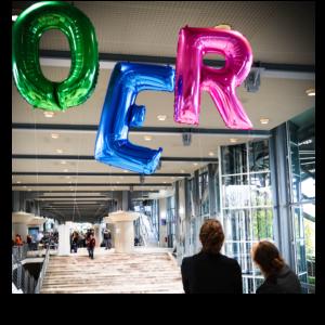 Die Buchstaben OER als bunte schwebende Gasballons oberhalb von zwei aufblickenden Personen.